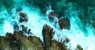 Antenne: mooie overzeese golven met wit schuim op rotsachtige kustlijn stock videobeelden