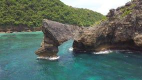 Antenne : Mouche autour de stupéfier Cliff Rock Arch Island en mer à la plage d'Atuh à Nusa Penida, Indonésie 4K banque de vidéos