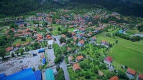 Antenne over dorp in groene heuvels en valleien wordt geschoten die stock video
