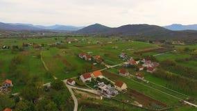 Antenne over dorp met huizen en groene valleien wordt geschoten die stock videobeelden