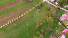 Antenne over dorp met huizen en groene valleien wordt geschoten die stock footage