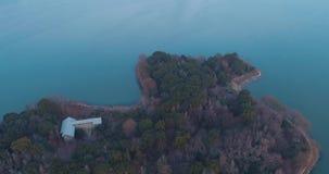 Antenne over eiland in het midden van blauw watermeer op de zonsondergang stock video