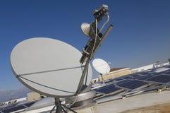 Antenne parabolique avec les panneaux solaires photographie stock