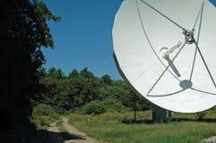 Antenne parabolique près de chemin de pays Image stock