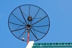 Antenne parabolique sur la tuile de toit verte Image stock