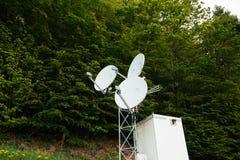 Antenne parabolique trois sur une tour de communication au milieu d'a Images stock