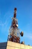 Antenne rouge et blanche (tour cellulaire) sous le ciel bleu. Image stock