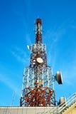 Antenne rouge et blanche (tour cellulaire) sous le ciel bleu. Photos libres de droits