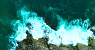Antenne: Schöne Meereswogen mit weißem Schaum auf felsiger Küstenlinie stock video footage