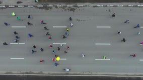 Antenne supérieure de bas des personnes courant au marathon de course de sports sur la route urbaine banque de vidéos