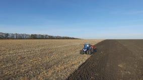 Antenne: tractor die bij zonsondergang het gebied in de herfst ploegen stock footage