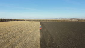 Antenne: tractor die bij zonsondergang het gebied in de herfst ploegen stock video