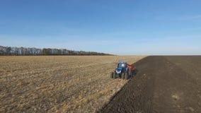Antenne: Traktor bei dem Sonnenuntergang, der das Feld im Herbst pflügt stock video