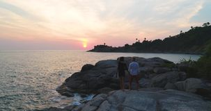Antenne : Un couple affectueux observant le coucher du soleil sur la mer sur les roches clips vidéos