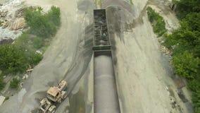 Antenne van arbeiders wordt geschoten die industrieel puin van ladingswagens die leegmaken stock videobeelden