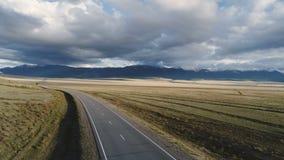 Antenne van auto wordt geschoten die de weg doorgeven tot de bergen die 4k stock footage