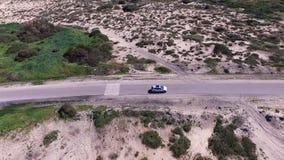 Antenne van auto wordt geschoten die op woestijnweg naderbij komen, Israël, Mediterrane kust die stock video