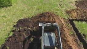 Antenne van bulldozer en graafwerktuig gravende stichtingskuil op grasrijk gebied stock footage