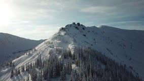 Antenne van de skiërski van de hommelmens het reizen in de sneeuwbergen bergop in een lijn stock videobeelden