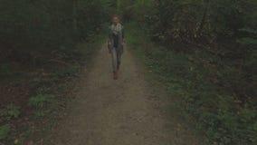 Antenne van een jonge vrouw die door een bos, lage hoogte volgend schot van links naar rechts lopen stock footage