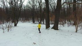 Antenne van gebaarde atleet in gele laag die met kabel in de winterbos overslaan stock video
