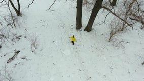 Antenne van gebaarde atleet in gele laag die met kabel in de winterbos springen stock footage