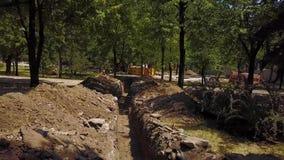 Antenne van gegraven geulen voor pijpleidingen en mededelingen bij een bouwwerf De wederopbouw van de waterpijpleiding en stock videobeelden