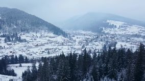Antenne van gewoonde in plaats in de bergen op de winter De gebouwen en de huizen van het bergdorp op sneeuwheuvelhellingen stock footage