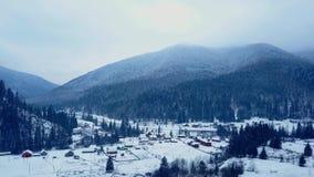 Antenne van gewoonde in plaats in de bergen op de winter De gebouwen en de huizen van het bergdorp op sneeuwheuvelhellingen stock video