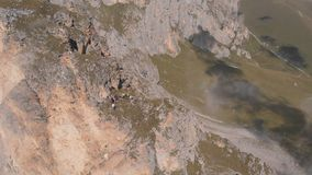 Antenne van groep klimmers wordt geschoten die met een kabel werken die Het reddingswerk die tot de bovenkant van de berg beklimm stock videobeelden