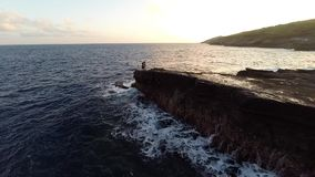 Antenne van korte klip tijdens zonsondergang met vissers stock video