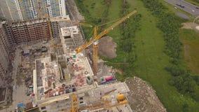 Antenne van kraan, technicals die van het bouw de nieuwe moderne bouwwerk bouwers en wordt geschoten stock video