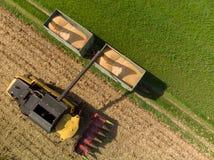 Antenne van maaimachinelading van graan op aanhangwagens wordt geschoten die royalty-vrije stock afbeelding