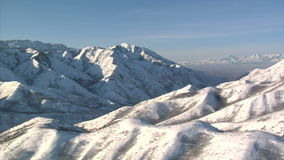 Antenne van sneeuwbergen met zoute meervallei wordt geschoten in de afstand die stock footage