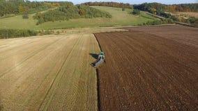 Antenne van tractor wordt geschoten die zwarte grond dicht bij bos de Herfstzonsondergang die ploegen stock videobeelden