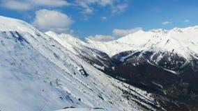 Antenne: vliegend over wandelaar op sneeuwbergbovenkant, ski het reizen de berg van de alpinismesneeuw, panorama op de alpen, het stock videobeelden