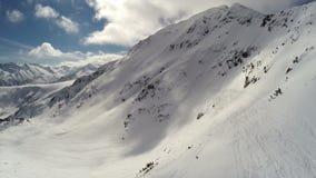 ANTENNE: Vlucht over berg met sneeuw wordt behandeld die stock footage