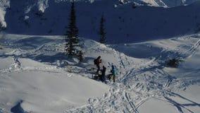 Antenne vom Brummenmann-Skifahrerski, der in die schneebedeckten Berge ansteigend in einer Linie bereist stock video