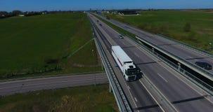 ANTENNE: Vrachtvrachtwagen die ladingscontainer op een weg vervoeren stock videobeelden