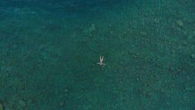 Antenne: vrouw die op blauwe waterspiegel drijven, die in transparante Middellandse Zee, top down mening, de zomervacatio zwemmen stock footage
