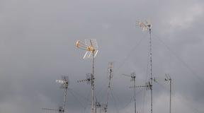 Antennen über den Dächern gegen grauen Himmel stockbild