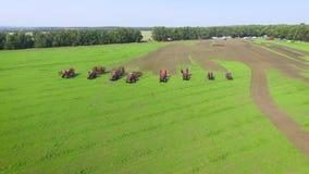 Antennen av att bruka maskiner visar att rida tillsammans på grönt fält i bygd lager videofilmer