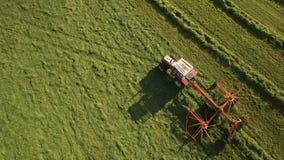 Antennen av traktoren gör höbaler och tappar dem som täckas i plast- på solig dag i bergen lager videofilmer