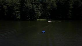 Antennen sköt av en cableway i en sjö med en wakeboarder arkivfilmer