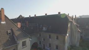 Antennen sköt av en ghosttown, medelspårningskott från rakt till vänstert framme av en sjaskig rad av hus som därefter stiger lån stock video