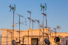 Antenner i aftonsolen på ett tak i Seville arkivfoton
