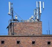 Antenner på överkanten av en gammal lagerbyggnad royaltyfri foto