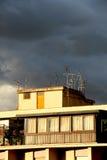 Antenner på ett tak, mot en molnig himmel Fotografering för Bildbyråer