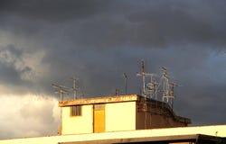 Antenner på ett tak, mot en molnig himmel Royaltyfria Bilder