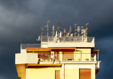 Antenner på ett tak, mot en molnig himmel Arkivfoton